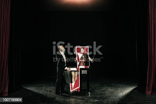 Magician performing trick with his assistant who is cut in half in the magic box