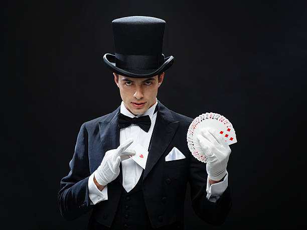 magician showing trick with playing cards magic, performance, circus, gambling, casino, poker and  show concept - magician in top hat showing trick with playing cards magician stock pictures, royalty-free photos & images