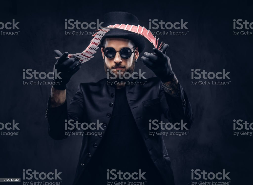 Magician showing trick with playing cards. stock photo