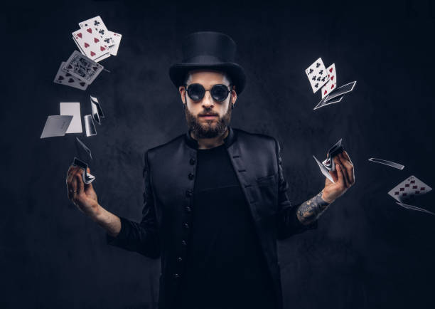 Magician showing trick with playing cards. Magician in a black suit, sunglasses and top hat, showing trick with playing cards on a dark background. magician stock pictures, royalty-free photos & images