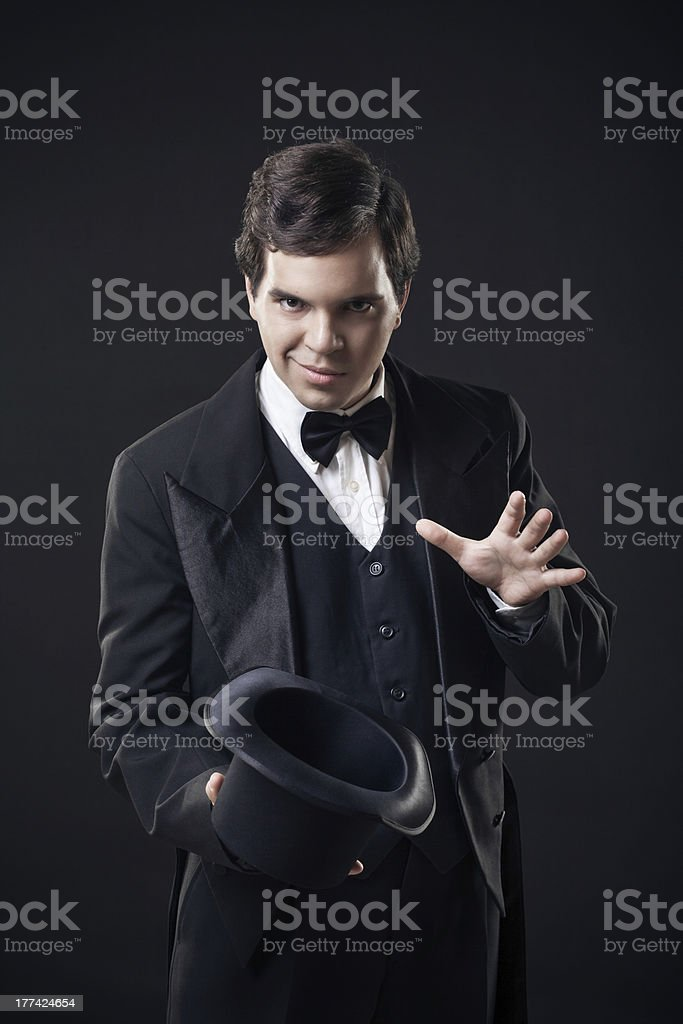 magician showing tricks with top hat isolated on dark background stock photo