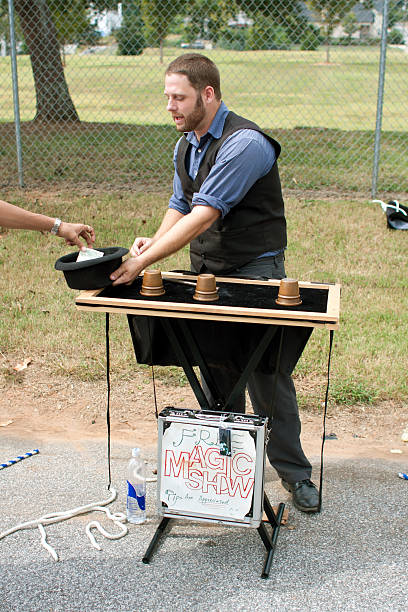 Magician Takes Tips While Performing At Festival Atlanta, GA, USA - September 29, 2012:  An unidentified magician accepts tips and entertains people  attending the Summerhill Fall Festival, a first-time event held in the streets of the Summerhill neighborhood in Atlanta. shell game stock pictures, royalty-free photos & images