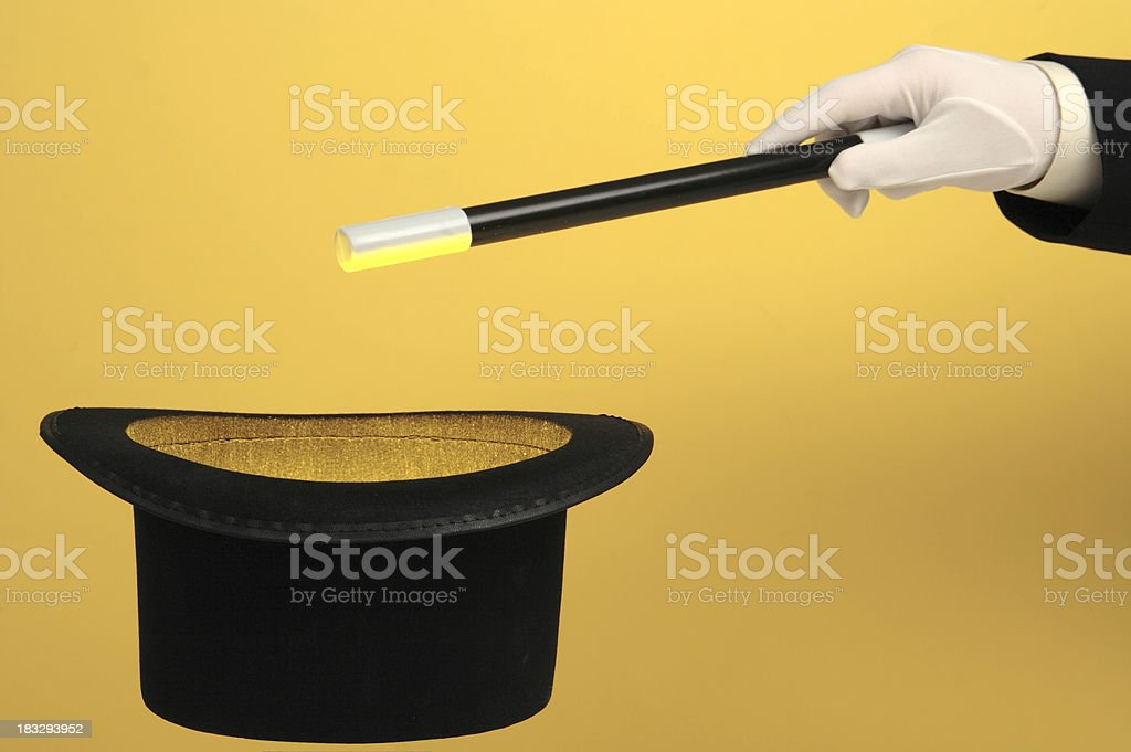 Magician Waving Wand over Glowing Top Hat stock photo