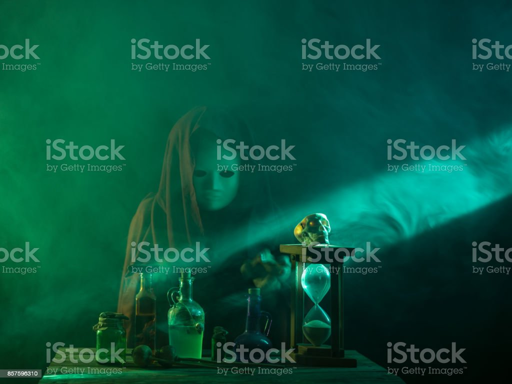 Magician Wearing Hooded Cloak With Mask Doing Magic For Halloween stock photo