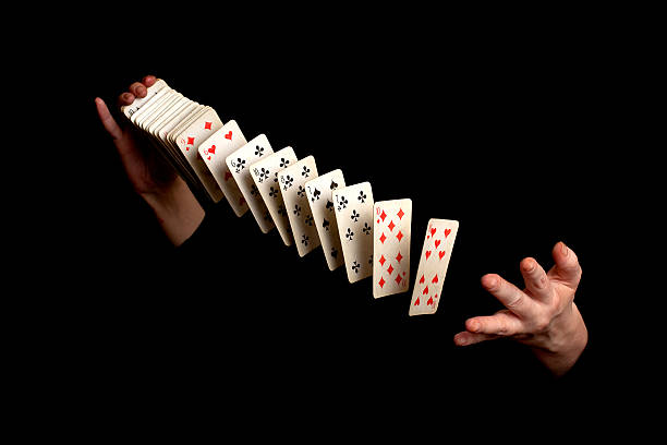 magician with cards on black background - magician stock photos and pictures