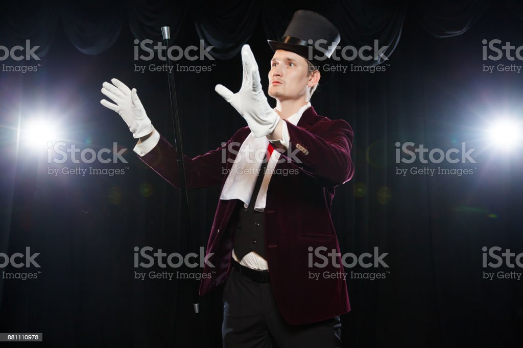Magician with fly ball, Juggler man, Funny person, Black magic, Illusion A focus with a levitating cane with a magic wand on a black background stock photo