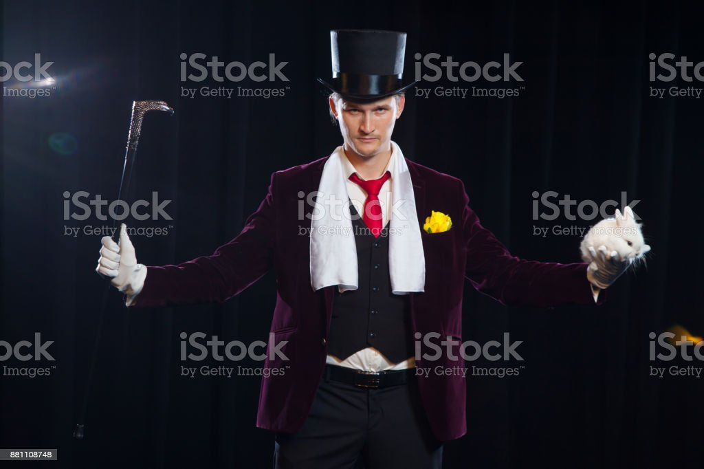 Magician with rabbit, Juggler man, Funny person, Black magic, Illusion on a black background stock photo