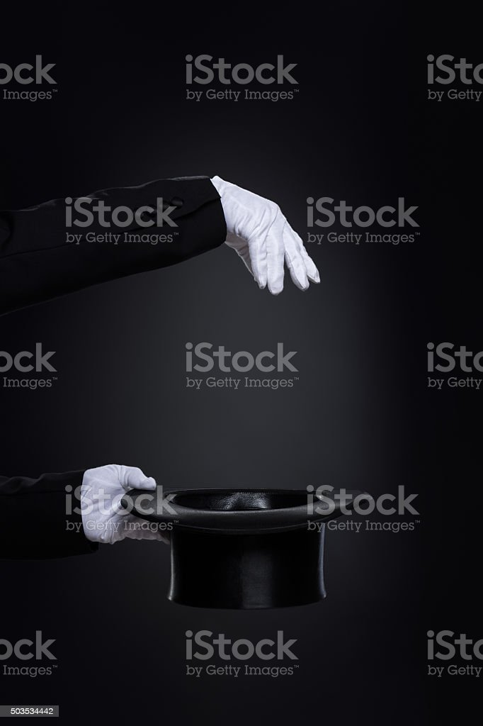 Magicianˈs hands in white gloves with top hat stock photo