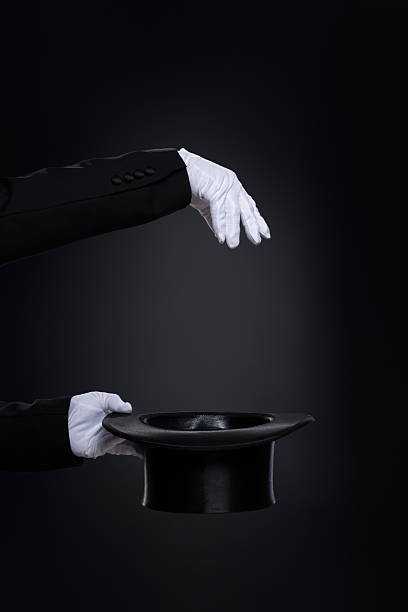 Magicianˈs hands in white gloves with top hat Magicianˈs hands in white gloves with top hat over black magician stock pictures, royalty-free photos & images