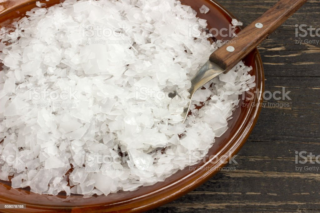 Magnesium chloride flakes in a saucer stock photo