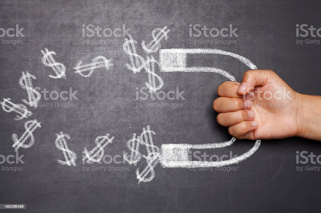 magnet attracting dollars stock photo
