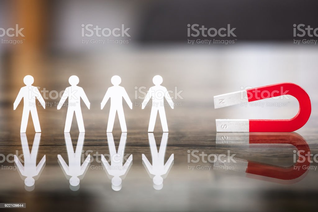 Magnet Attracting Paper Cut Out Standing In Row stock photo