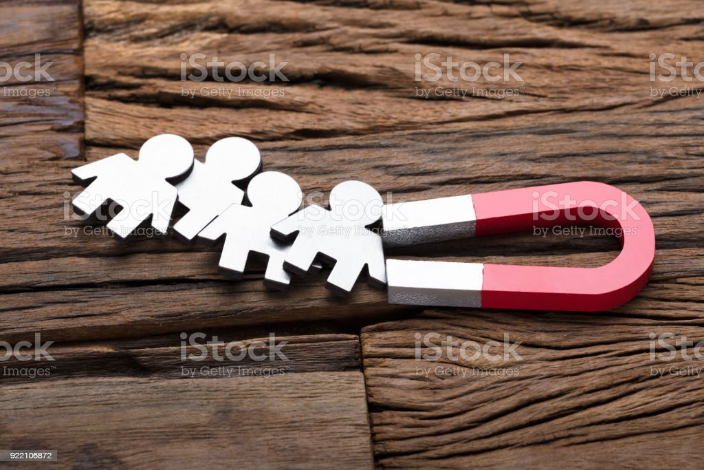 Magnet Attracting People On Wood stock photo