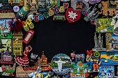 Travel memories. Magnet souvenir for fridge on black background. Where to go?
