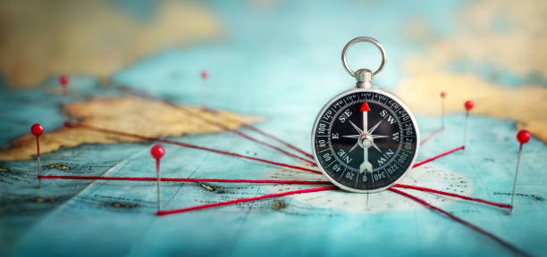 Magnetic compass  and location marking with a pin on routes on world map. stock photo