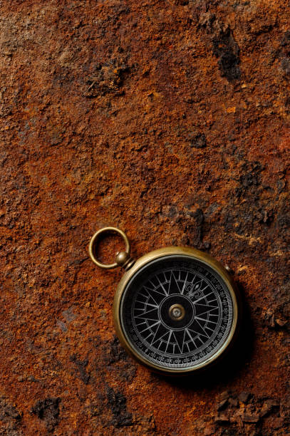 Magnetic compass on rough rusty background stock photo