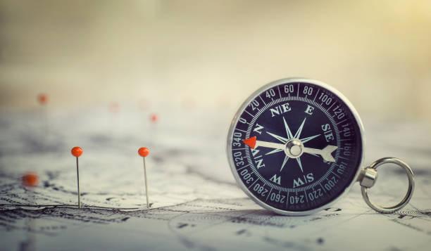 magnetkompass auf weltkarte. - kartographie stock-fotos und bilder
