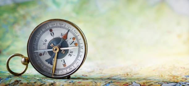 magnetic old compass on world map. - navigational compass stock photos and pictures