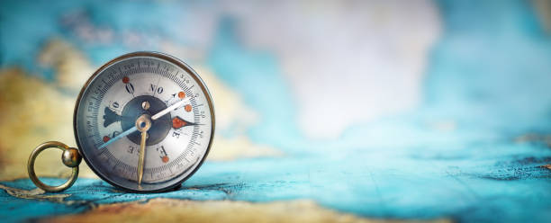 Magnetic old compass on world map. Magnetic old compass on world map.Travel, geography, navigation, tourism and exploration concept wide background. Macro photo. Very shallow focus. navigational equipment stock pictures, royalty-free photos & images