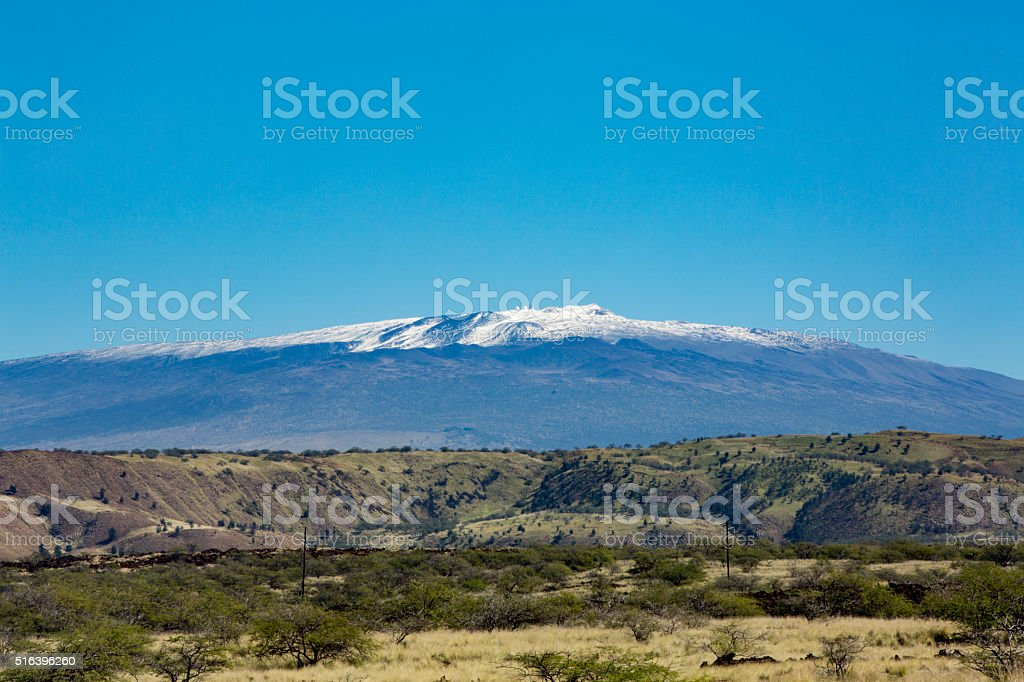 Magnicent and Snow Capped Mauna Kea Looms over the Landscape stock photo
