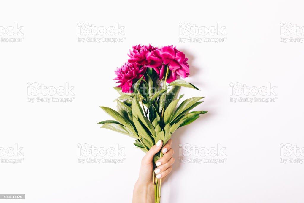 Magnifique bouquet de pivoines lumineux dans une main de femme sur fond blanc - Photo