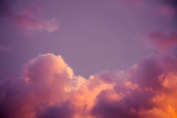 Magnificent colorful clouds in the evening sky. Bright, pink clouds in the sky at sunset. Beautiful evening skyscape. Abstract, purple pink background. stock photo