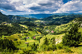 Magnificent sweeping landscape scene in Transylvania, Romania. Rolling green hills and the Carpathian mountains surround picturesque villages in the valley below. Wide angle horizontal image.