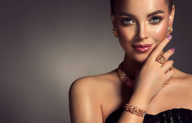 Magnificent lady in a perfect make up is shows jewelry set. stock photo