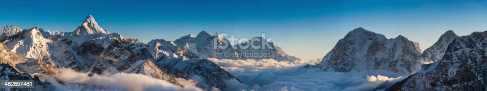 The iconic snow capped spire of Ama Dablam illuminated by the golden light of a high altitude sunset overlooking the clouds in the Khumbu mountain valley below, Mt. Everest National Park, Himalayas, Nepal. ProPhoto RGB profile for maximum color fidelity and gamut.