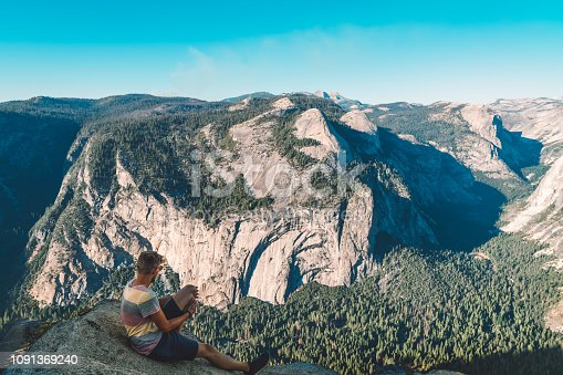Young caucasian man went on a backpacking trip trough USA. Happy hiker in Yosemite valley, magnificent view over the Yosemite valley.
