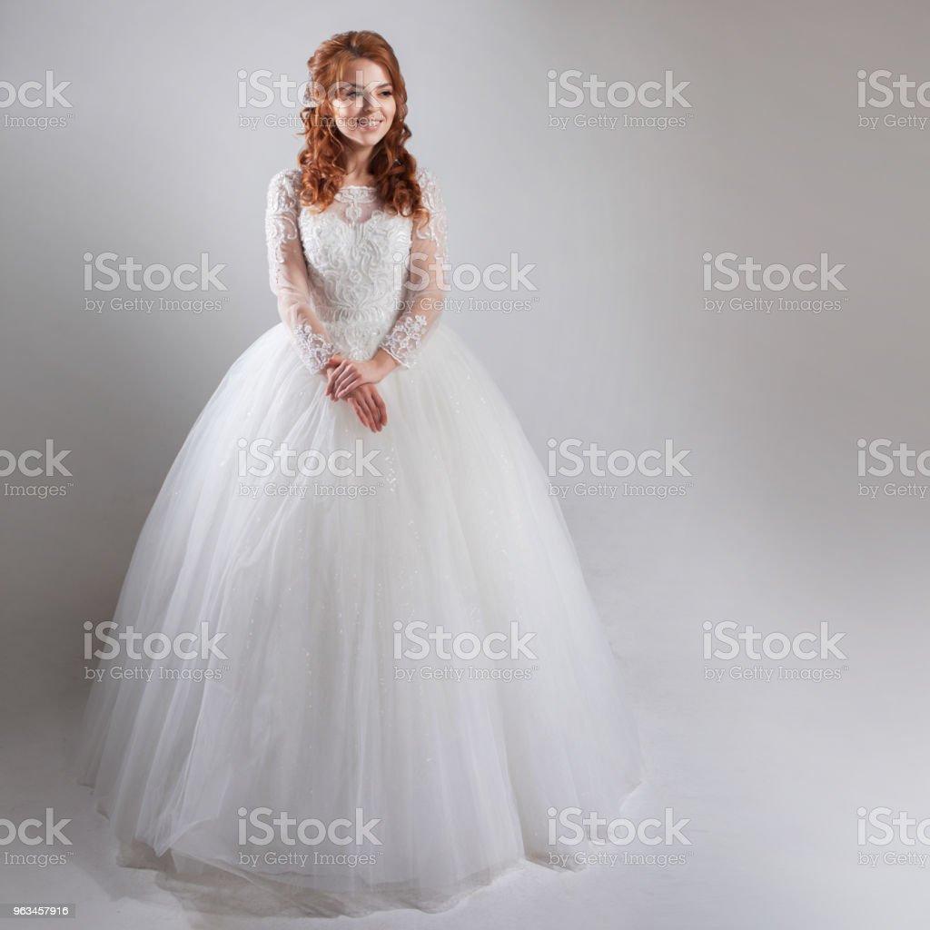 Wspaniała suknia ślubna z krynoliną, klasycznym stylem. Kobieta panna młoda w wystawnej sukni ślubnej. Lekkie tło. - Zbiór zdjęć royalty-free (Ceremonia)