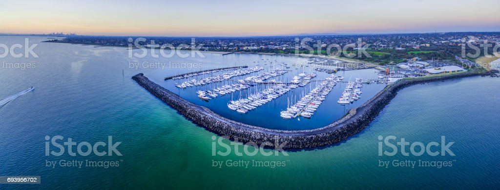 Magnificent wide aerial panorama of a beautiful Marina with moored sailboats and Melbourne coastline at dusk stock photo