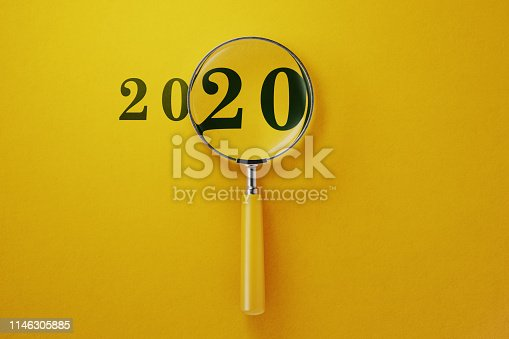 Magnifier and 2020 on yellow background. Horizontal composition with copy space.