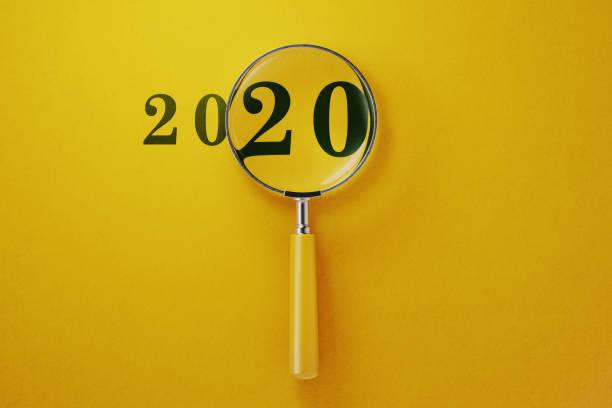 loupe et 2020 sur fond jaune - 2020 photos et images de collection