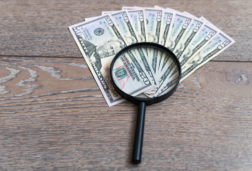 Magnifier and dollars on wood background