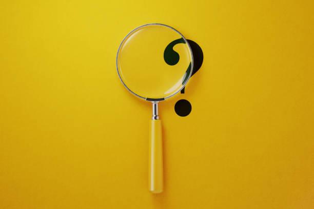 黃色背景上的放大鏡和問號 - 專長 個照片及圖片檔