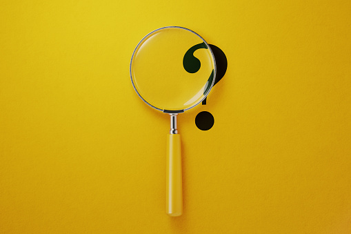 Magnifier And Question Mark On Yellow Background Stock Photo - Download Image Now