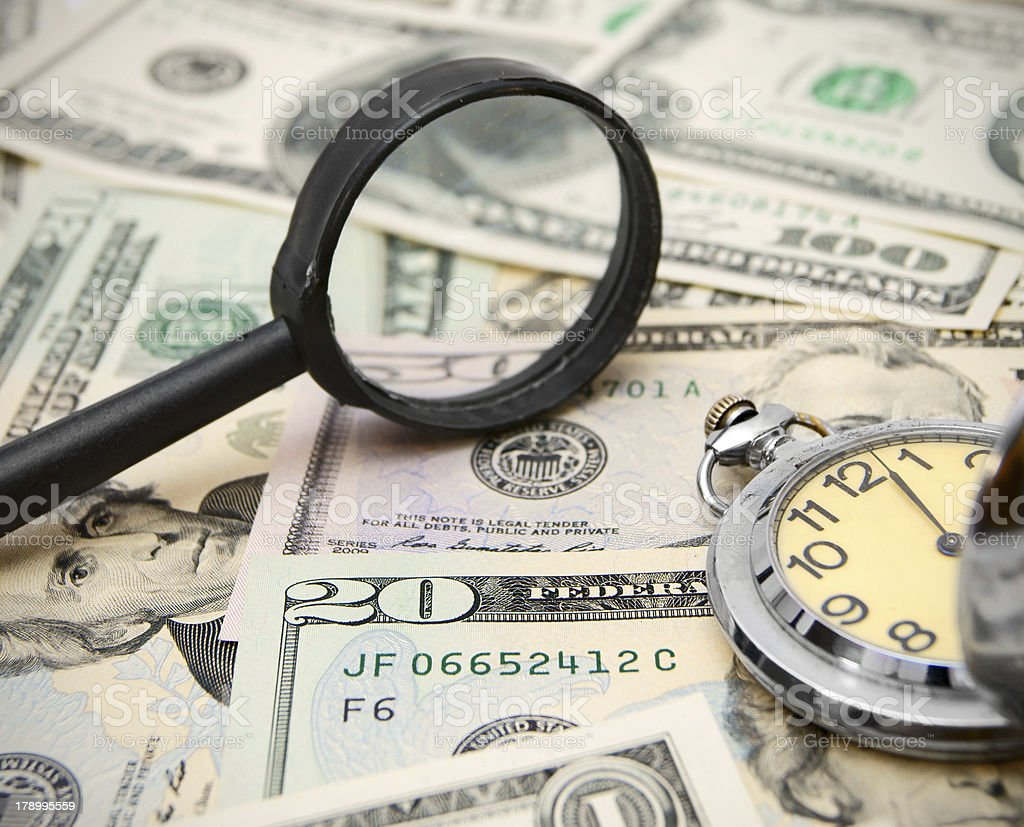 Magnifier and watches on dollars. royalty-free stock photo