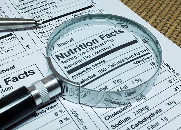 magnifier highlighting nutrition facts of foods - ingrediënt stockfoto's en -beelden