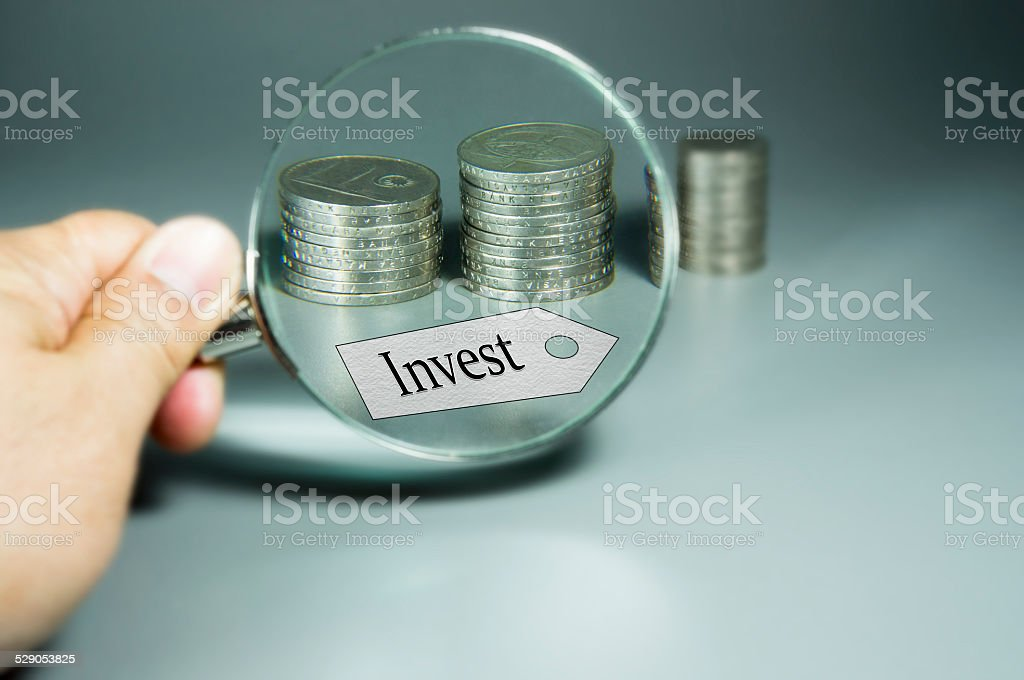 Magnifier, Invest Tag, and Stack of Coins in the backdround stock photo