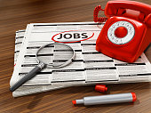istock Magnifier on job word on the newspaper. Rotary phone, marker and newspaper on the wooden table 1183937415
