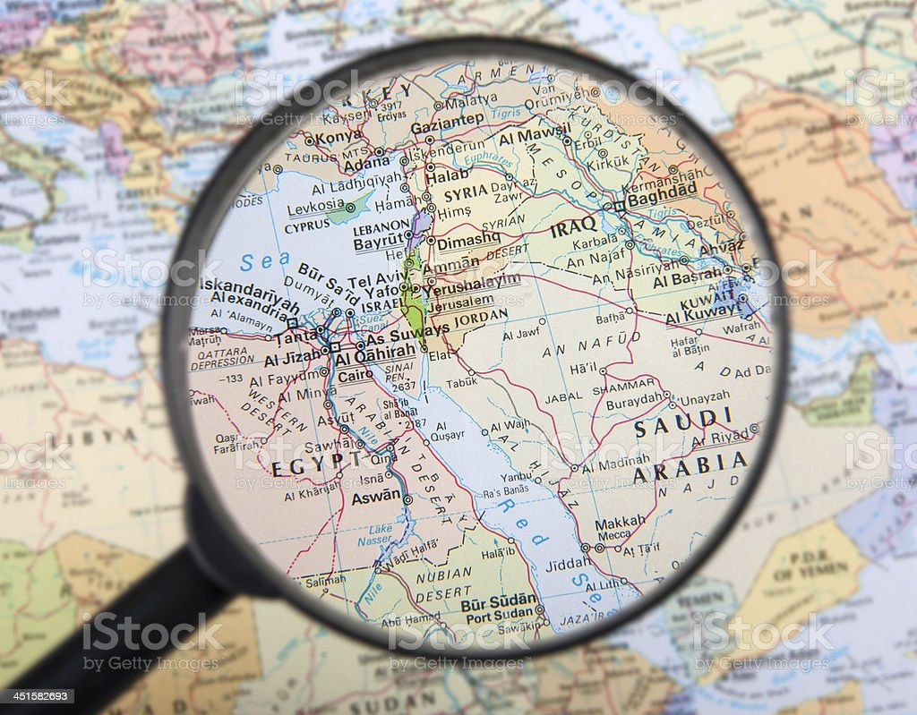 a magnifier zooming in middle east countries on a global map royalty free stock photo