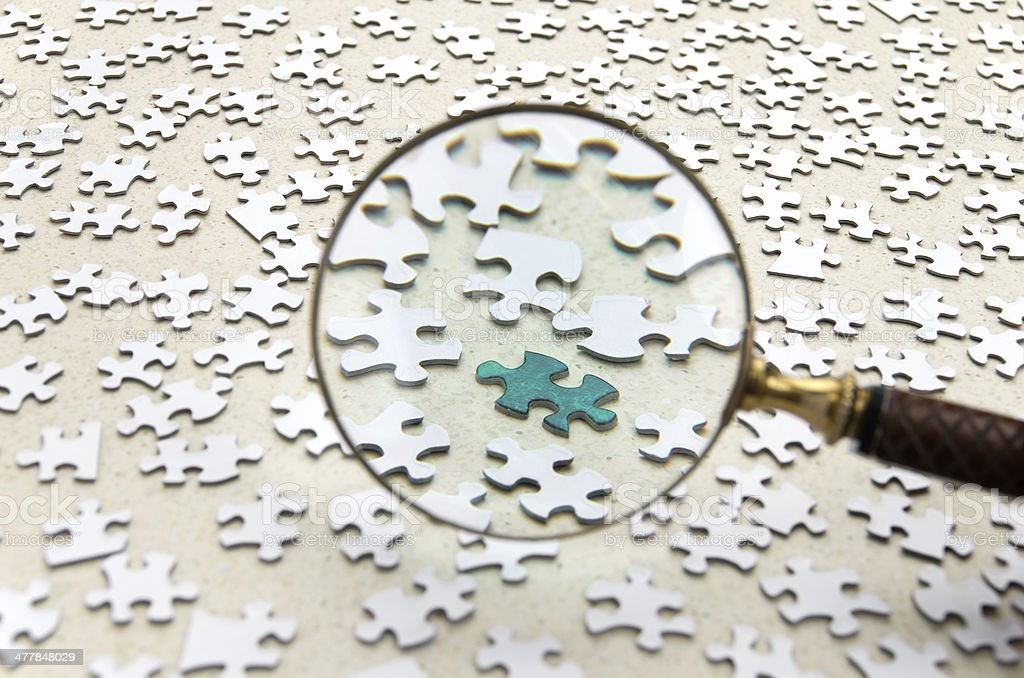 Magnifiying Glass and Jigsaw Puzzle stock photo