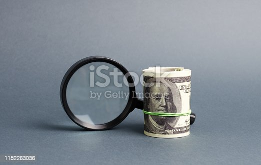 istock Magnifying glass and a bundle of money. Concept of fundraising, attracting investments. Loan to paycheck, urgent loans. The study of sources of profit, money laundering, offshore. Financial monitoring 1152263036