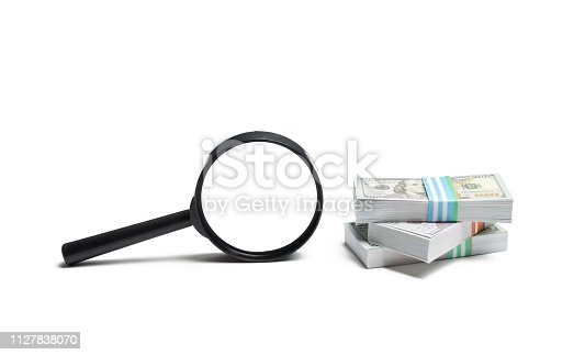 istock Magnifying glass and a pile of money. Concept of fundraising, attracting investments. Loan to paycheck, urgent loans. The study of sources of profit, money laundering, offshore. Financial monitoring 1127838070