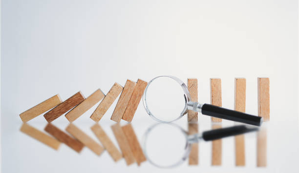 Magnifying glass and amidst  wooden block. Magnifying glass and amidst  wooden block. Risk Management concept. amidst stock pictures, royalty-free photos & images