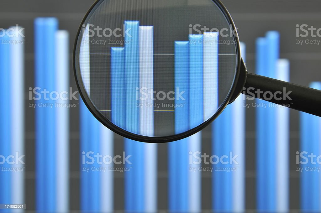 Magnifying glass and chart pictured on computer stock photo