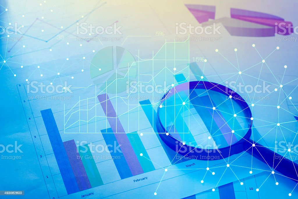 Magnifying glass and documents with analytics data lying on tabl royalty-free stock photo