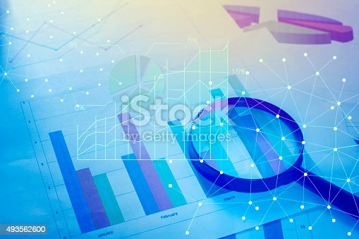 istock Magnifying glass and documents with analytics data lying on tabl 493562600
