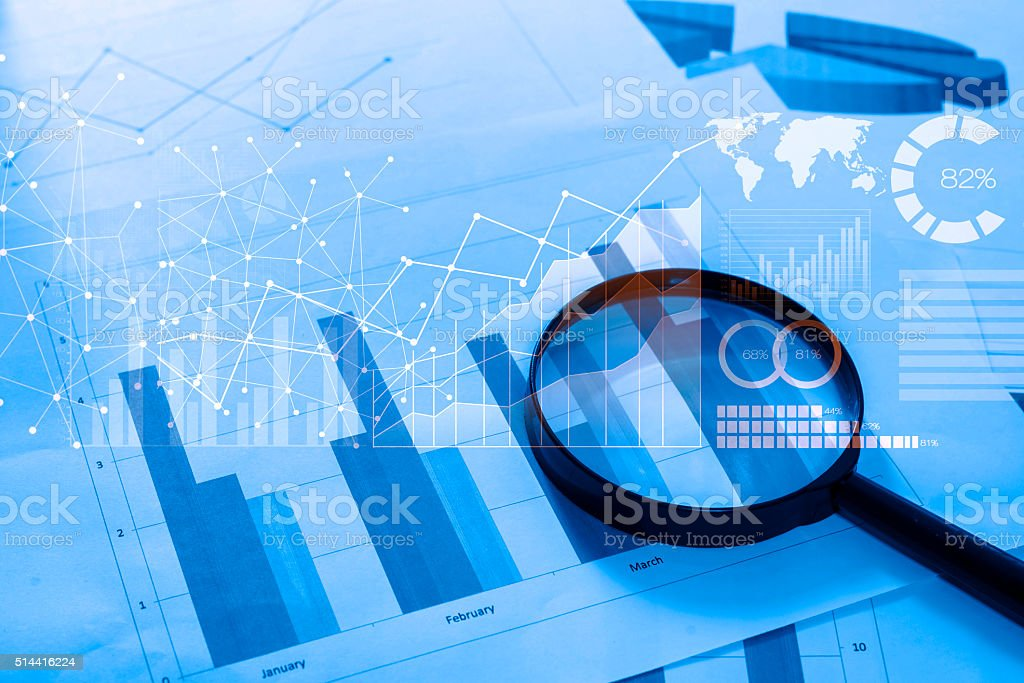 Magnifying glass and documents with analytics data lying on tabl bildbanksfoto